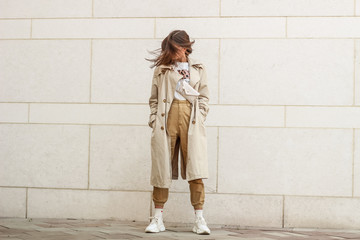 Portrait shooting of a stylish girl. Beige shades. Trends of spring and summer 2019. Pants of cork.Trench cloak, a wide jacket. Wall mural
