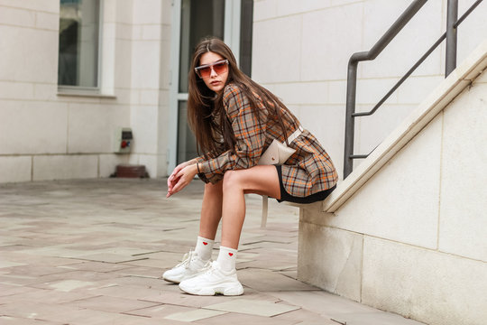 Portrait shooting of a stylish girl. Beige shades. Trends of spring and summer 2019. Wide jacket and belt leather bag. White sneakers and bike shorts