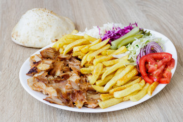 Chiken Doner Kebab on the plate with bread, french fries, tomatoes, onion, pickles and salad on a wooden background. Grilled chicken meat with vegetables.