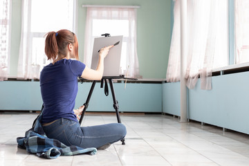 A girl artist with a palette knife in her hands is preparing to paint an oil painting..White canvas with copy space is located on the black easel.