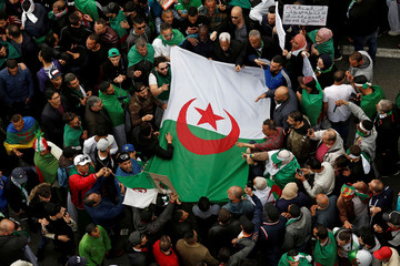Demonstrators hold flags and banners as they return to the streets to press demands for wholesale democratic change well beyond former president Abdelaziz Bouteflika's resignation in Algiers