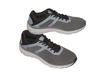 A pair of gray sports sneakers from above on a white isolated background