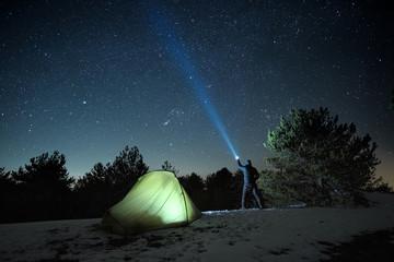 Man Pointing Blue Flashlight To Starry Sky