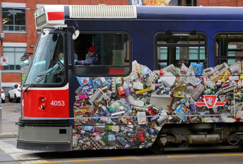 A TTC streetcar is seen covered with pictures of paper, plastic and metal containers to promote recycling in Toronto