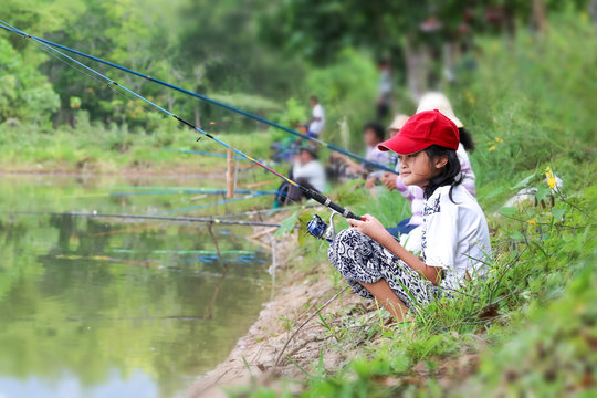 Asian girl enjoying to use a fishing rod by the canal or river.