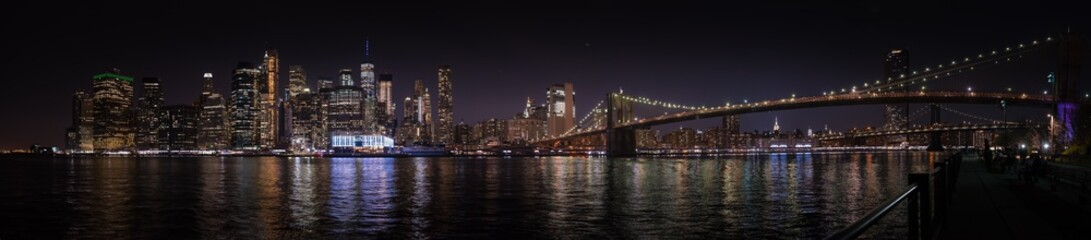 A large panoramic nighttime view of Manhattan and the Brooklyn Bridge from the opposite river bank