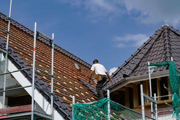 Dachziegel werden durch einen Dachdecker auf einen Neubau befestigt