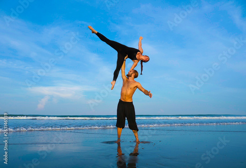 healthy and attractive fit couple of acrobats doing acroyoga