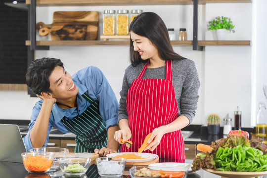 Man makes eye contact with woman in kitchen.