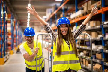 Obraz Positive people having fun at work. Warehouse workers pushing carts and enjoying in storage room. - fototapety do salonu