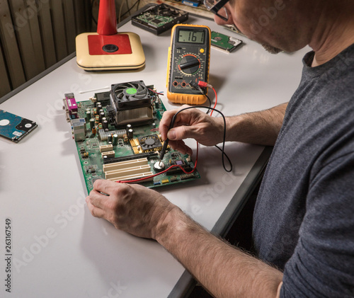 electronics technician is testing a computer chip  PC repair