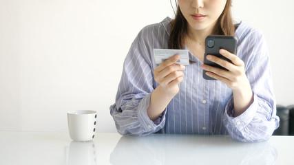 スマホとカードを見る女性
