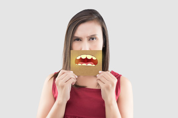 Asian woman in the red shirt holding a brown paper with the yellow teeth cartoon picture of his mouth against the gray background, Bad breath or Halitosis, The concept with healthcare gums and teeth