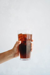 Hand holding a glass of homemade cold brew coffee on white table