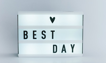 Photo of a light box with text, BEST DAY, over isolated wall background