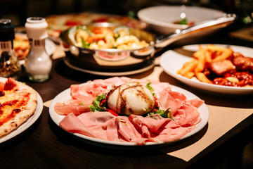 Cold Cuts Burratina: Burrata Cheese served with Parma Ham, Mortadella and Salad. Served in white plate on paper mat.