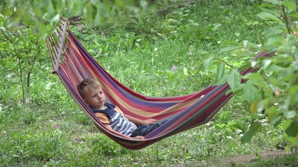 Cute little boy relaxing on colored hammock in green nature
