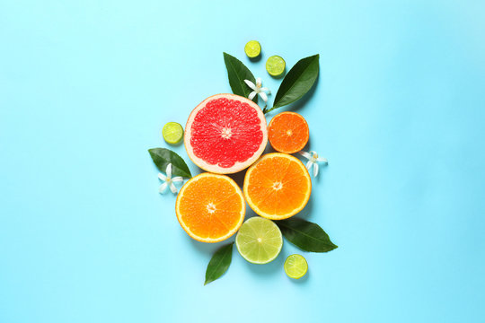 Flat lay composition with citrus fruits, leaves and flowers on color background
