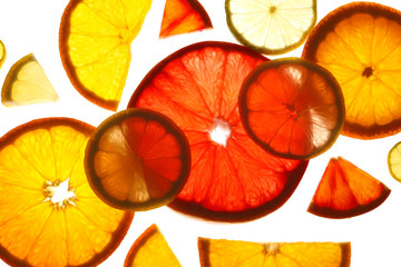 Illuminated slices of citrus fruits on white background, top view