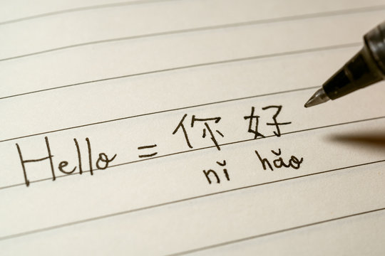 Beginner Chinese language learner writing Hello word Nihao in Chinese characters and pinyin on a notebook
