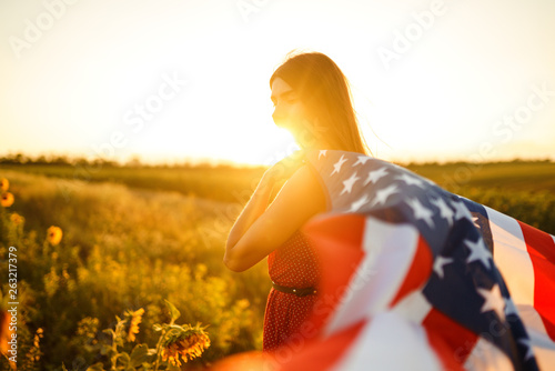 Beautiful girl in hat with the American flag in a sunflower field. 4th of July. Fourth of July. Freedom. Sunset light The girl smiles. Beautiful sunset. Independence Day. Patriotic holiday.