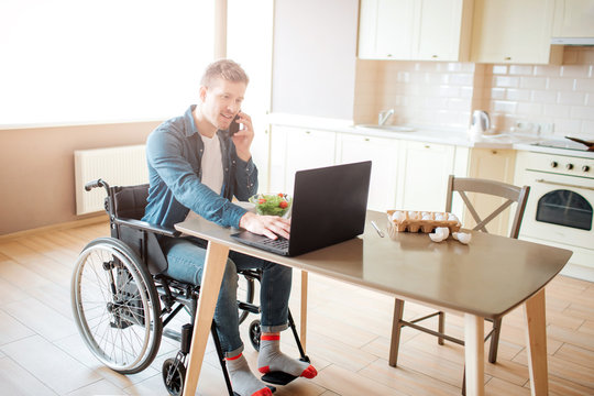 Young worker with disability and special needs sit at table and work. He use laptop and talk on phone. Alone in kitchen. Serious and concentrated.