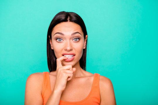 Close up photo portrait of depressed negative expressing nervous girl biting nails damaging new manicure isolated pastel background