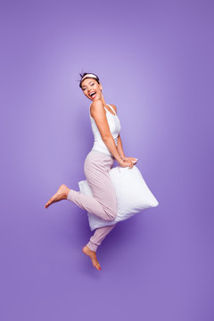 Vertical full length side profile body size photo beautiful she her lady jump hold between legs pillow naked nude feet foot wear sleeping mask pants tank-top pajamas isolated violet purple background