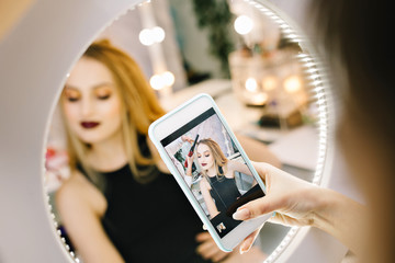 Elegant pretty young woman making photo on phone in mirror during making hairstyle in hairdresser salon. Stylish fashionable model, preparing to party, celebration, luxury look