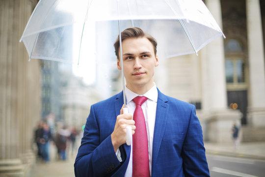 Elegant man walking under the rain in the street