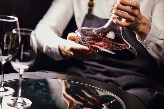 Cropped view of professional sommelier holding mixing bowl with red wine in hands over the table in wine restaurant.