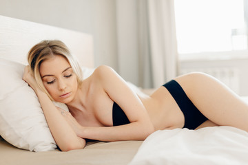 Sleeping half-naked blonde beauty lying on bed uncovered, in erotic manner, let us to see her seductive shapes and curves