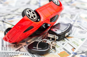 Overturned red car toy with car key on background of dollar bills. Car accident.