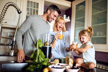Cheerful girl with parents in kitchen