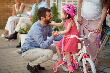 Young cheerful father buying new bicycle for little girl in bike shop .
