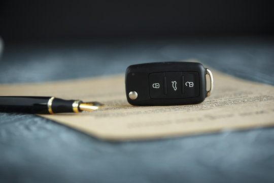 Black car key and money on a signed contract