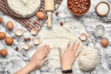 Close-up shot. Top view of a baker cook place, hands are working with a raw dough on the marble table background.