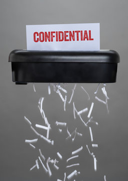 A shredder destroying a document - Confidential