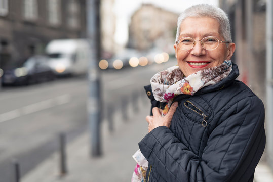 Portrait of beautiful senior woman with a jacket on a windy day in an urban city environment, happy and cheerful