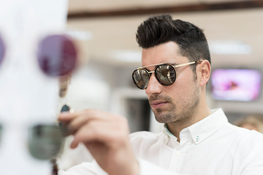 Man looking for buy sunglasses in store