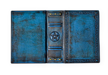 Aged blue leather book cover with the embossed Pentagram, ancient pagan symbol - lay down to the table opened and isolated