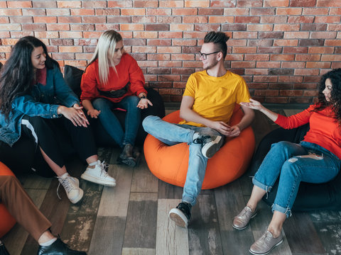 Casual business meeting. Creative millennials team relaxing in lounge area. Man women talking, sharing ideas. Leisure time.