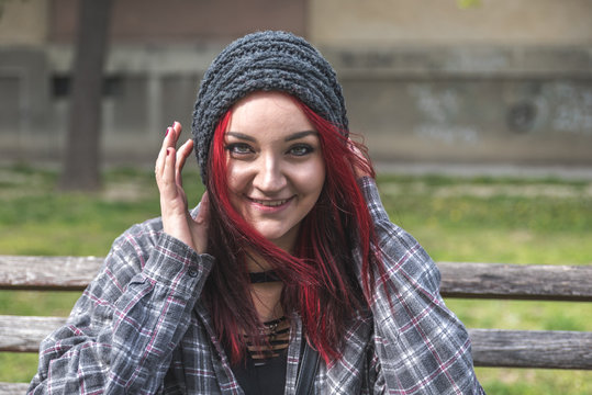Positive smiling homeless red hair girl sitting on the bench on the street and looking in the camera  while she having fun