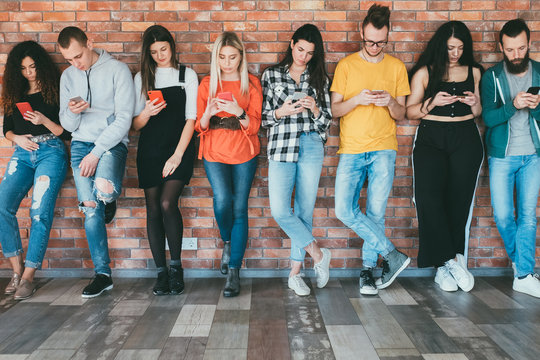 Always connected. Social networking. Group of millennials with smartphones surfing, chatting. Digital communication.