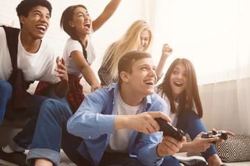Teenagers having fun, playing video games online