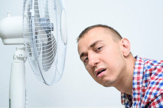 Man with stubble on his face suffers from the heat and trying to cool off near the fan.
