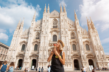 Happy traveler girl in Milan city. Tourist woman posing near Duomo cathedral in Milan, Italy, Europe
