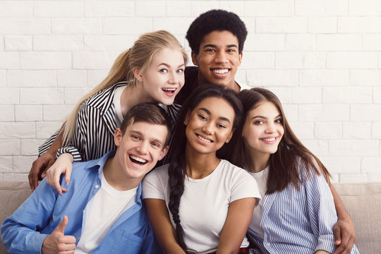 Happy diverse friends relaxing on comfortable couch in apartment