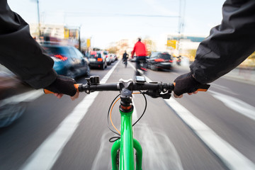 Cyclist drives on the bike path past the traffic jam - First-person view of cyclist/ motion blur Fototapete