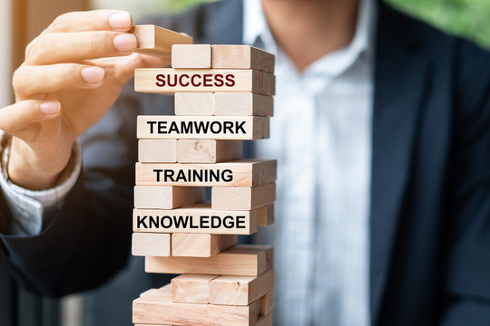 Businessman hand placing or pulling wooden block on the tower with text; Success, Teamwork, Training and Knowledge. Business concepts